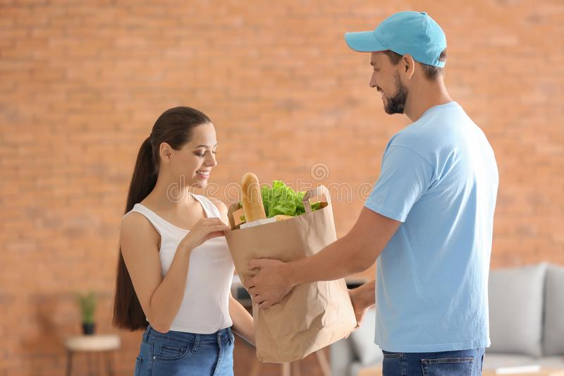 Man delivering food to customer indoors stock images