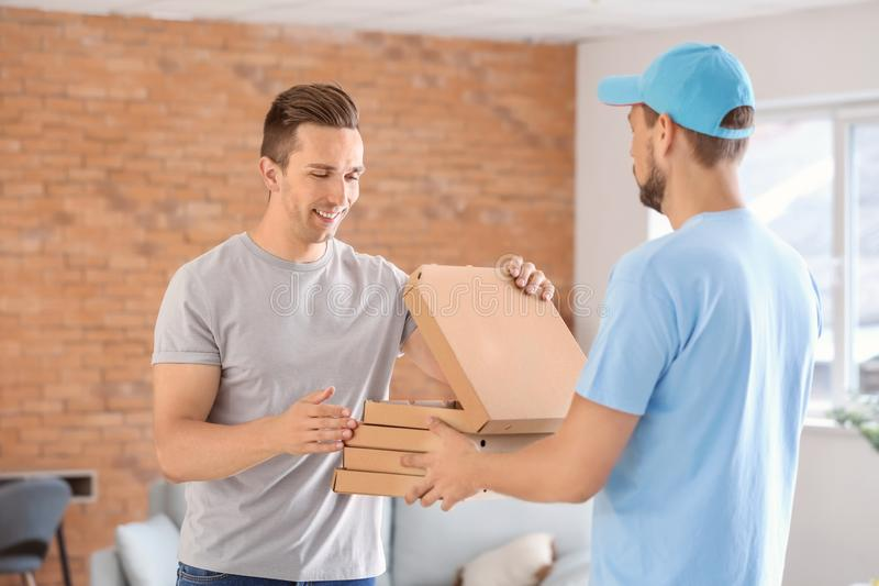 Man delivering pizza to customer indoors royalty free stock photography