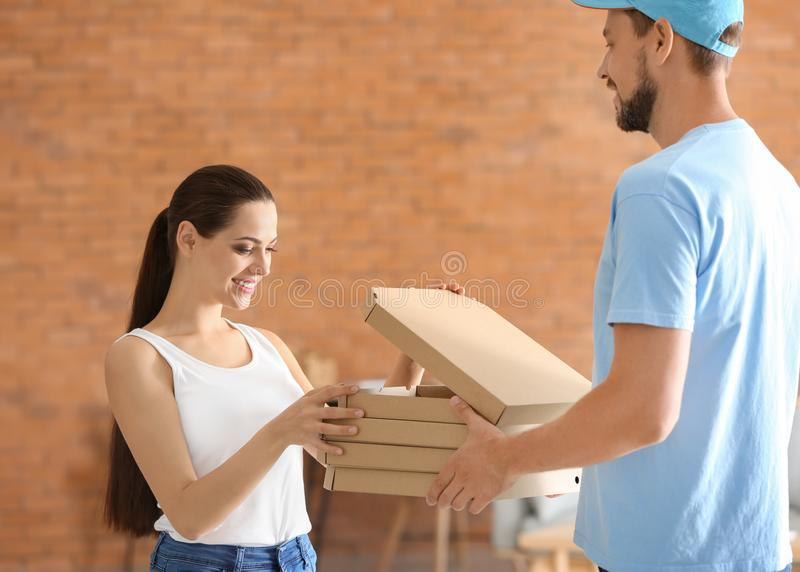 Man delivering pizza to customer indoors royalty free stock image