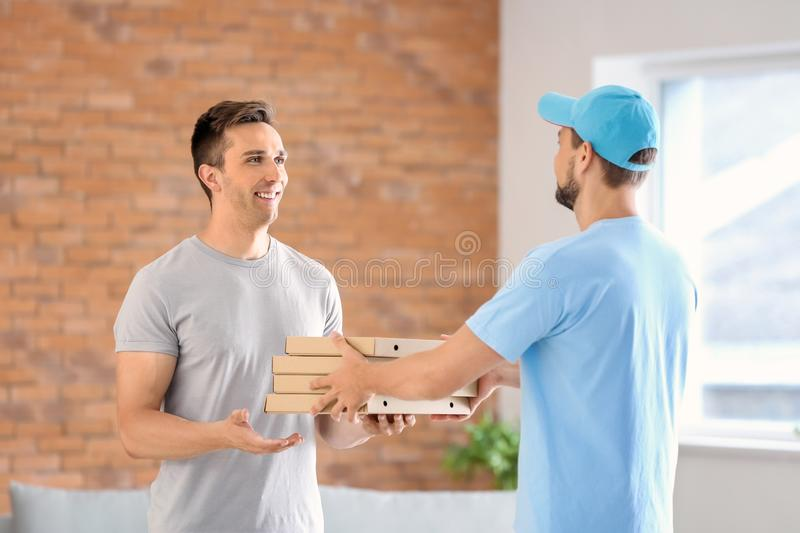 Man delivering pizza to customer indoors stock image