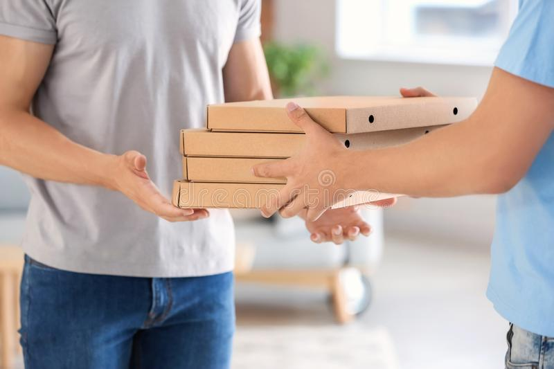 Man delivering pizza to customer indoors, closeup royalty free stock image