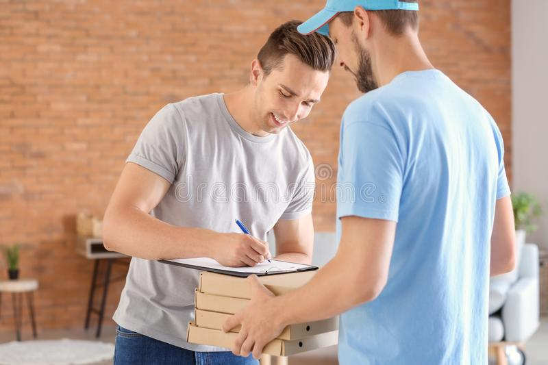 Man delivering pizza to customer indoors stock photography