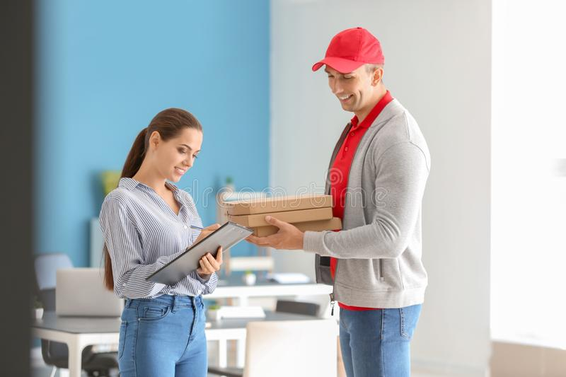 Man delivering pizza to customer indoors royalty free stock images