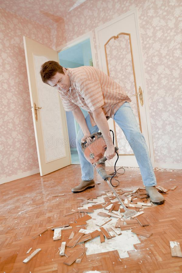 Man demolishing a floor. Man royalty free stock image