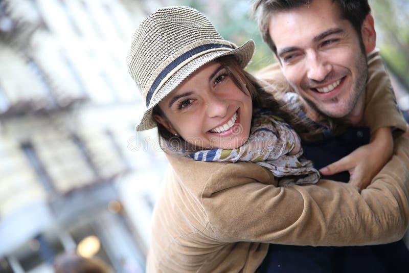 Man den bärande kvinnan på hans baksida i gatan royaltyfri foto