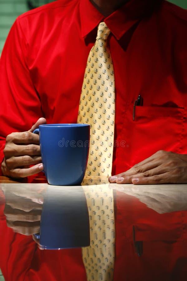 Man den bärande röda långa muffskjortan, gul slips, och innehavet som ett kaffe rånar royaltyfria bilder