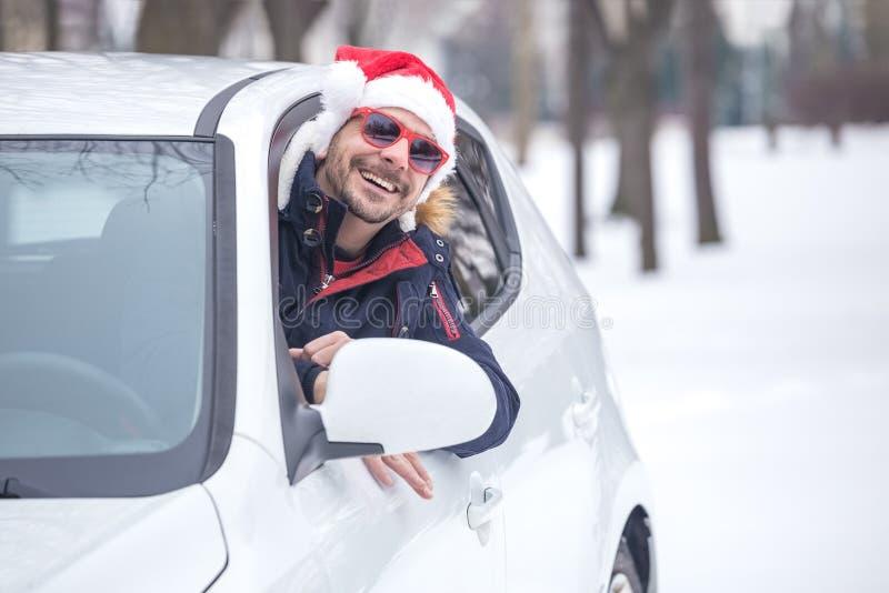 Man den bärande Santa Claus hatten och benägenheten på bilfönster Vinterloppbegrepp royaltyfri bild