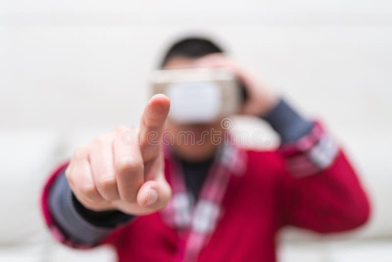 Man den bärande VR-exponeringsglas- eller virtuell verklighethörlurar med mikrofon med hans finger som hemma känner simuleringsvä arkivbild