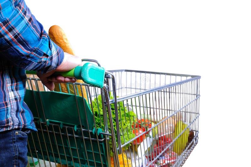 Man den driftiga shoppingvagnen mycket av mat isolerad vit arkivfoto