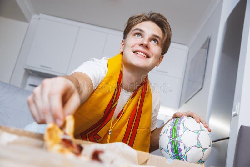 Man den hållande ögonen på sporten på ensam ätapizza för tv hemma arkivbilder
