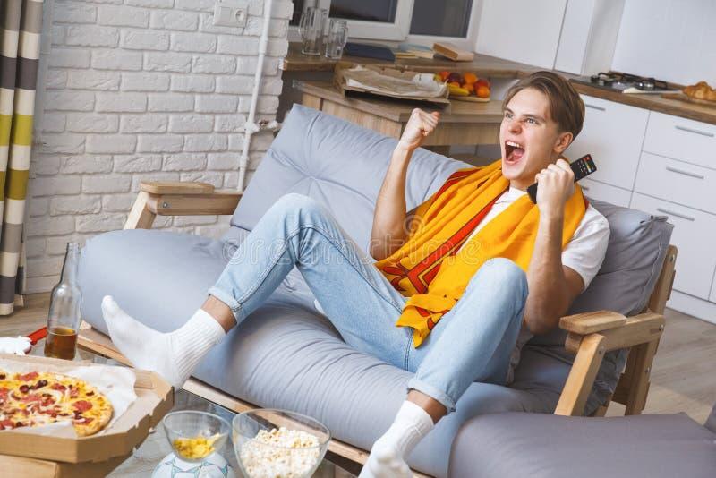 Man den hållande ögonen på sporten på ensam seger för tv hemma fotografering för bildbyråer