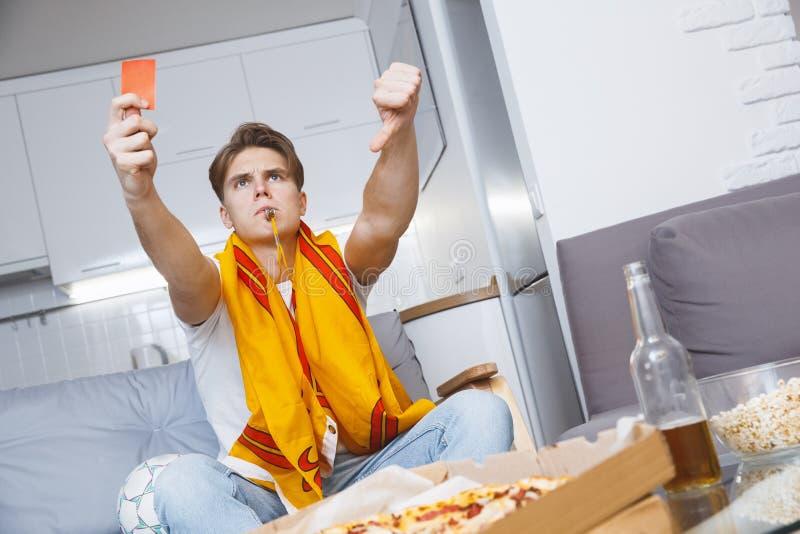 Man den hållande ögonen på sporten på ensamt rött kort för tv hemma royaltyfria bilder