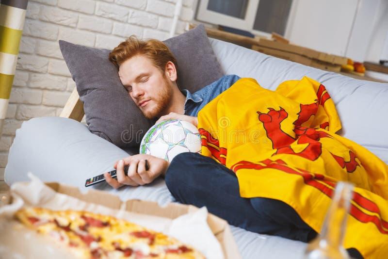 Man den hållande ögonen på sporten på ensamt sova för tv hemma fotografering för bildbyråer