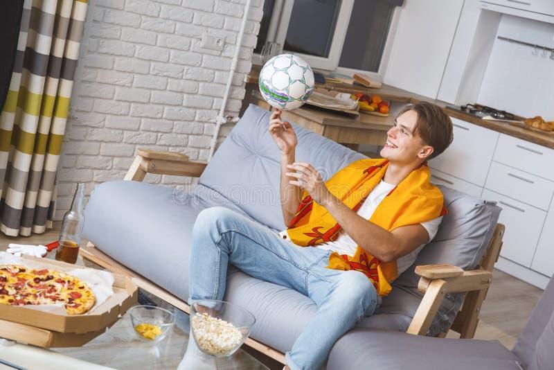 Man den hållande ögonen på sporten på ensamt spela för tv hemma med bollen royaltyfri foto