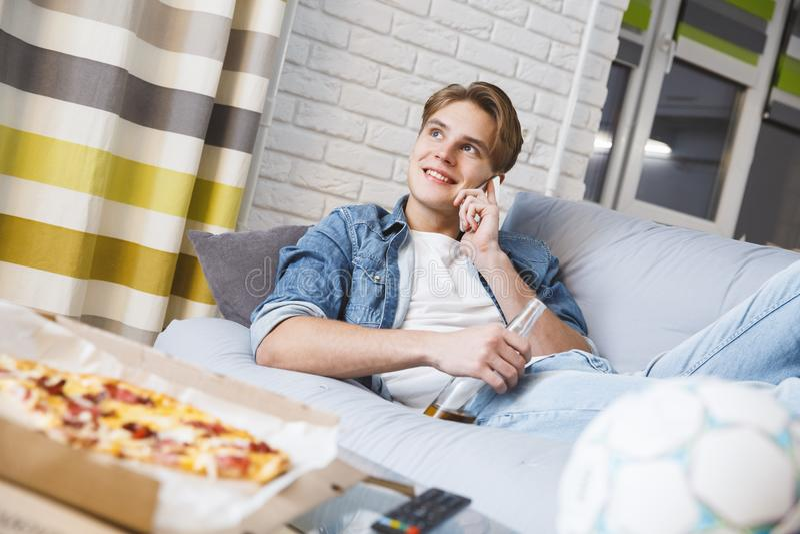 Man den hållande ögonen på sporten på hemmastadd ensam påringning för tv royaltyfria bilder