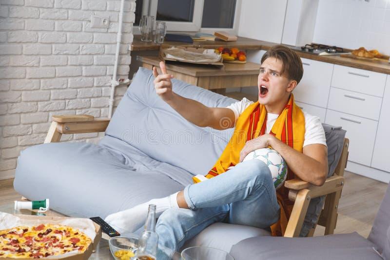 Man den hållande ögonen på sporten på olycklig tv hemma bara royaltyfria foton