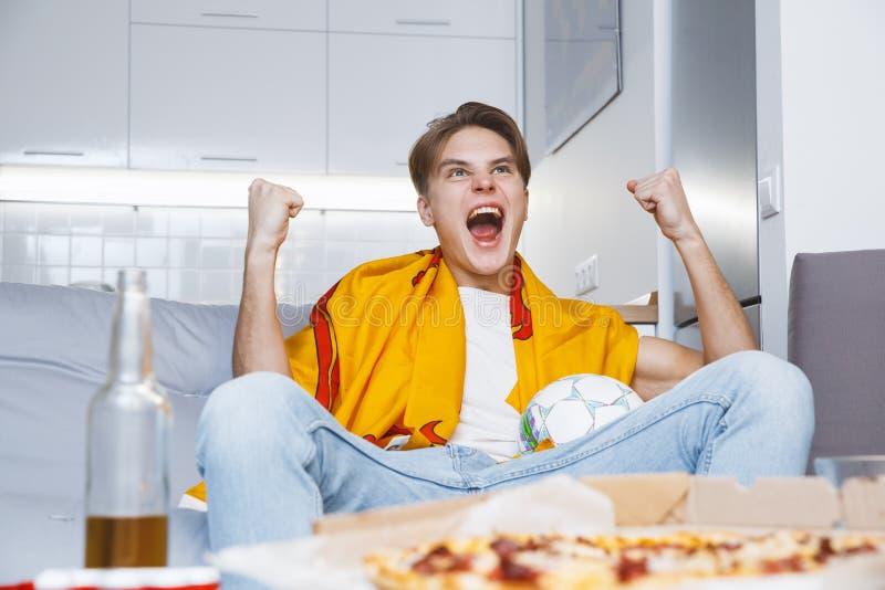 Man den hållande ögonen på sporten på sikt för ensam seger för tv hemma nedersta arkivfoto