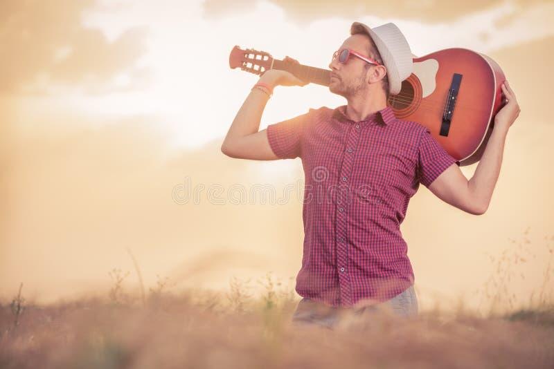 Man den hållande akustiska gitarren bak hans hals utomhus arkivbild