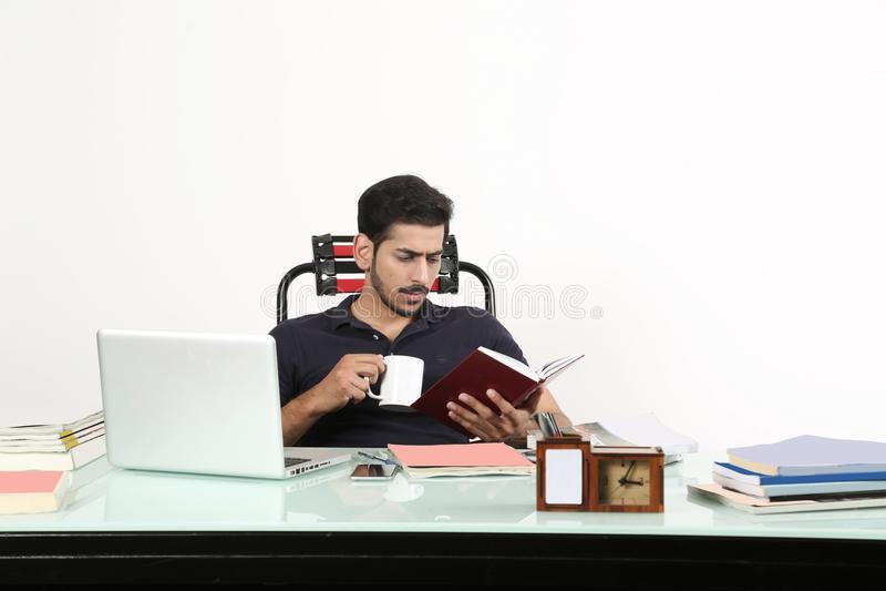 Man den hållande dagbok- och kaffekoppen i hand arkivfoton