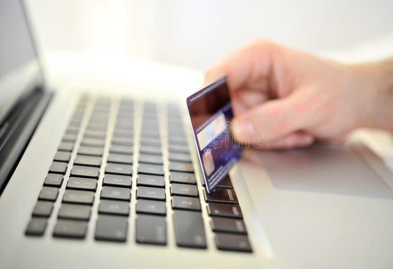 Man den hållande kreditkorten i handonline-shopping och bankrörelsen royaltyfri bild