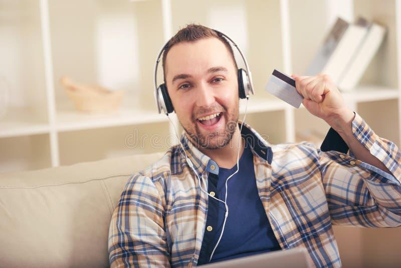Man den hållande kreditkorten och användabärbara datorn för online-shopping royaltyfri foto