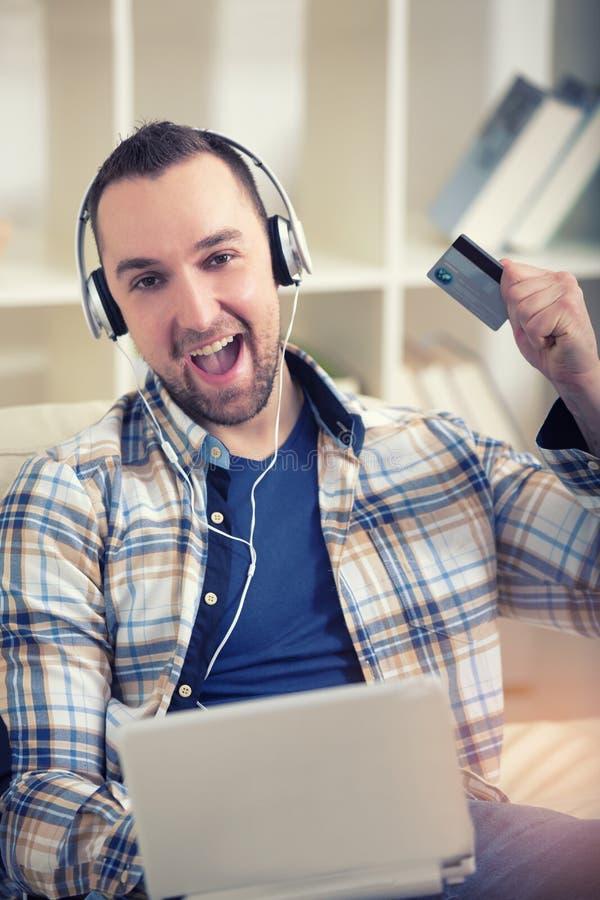 Man den hållande kreditkorten och användabärbara datorn för online-shopping royaltyfria bilder
