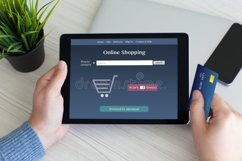 Man den hållande minnestavladatoren med online-shopping och kreditkorten arkivbilder
