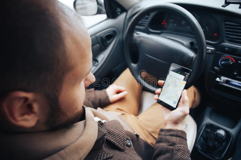 Man den hållande mobiltelefonen för chauffören med gps-applikationen i hans bil, modern navigeringteknologi för lopp och körnings arkivbild