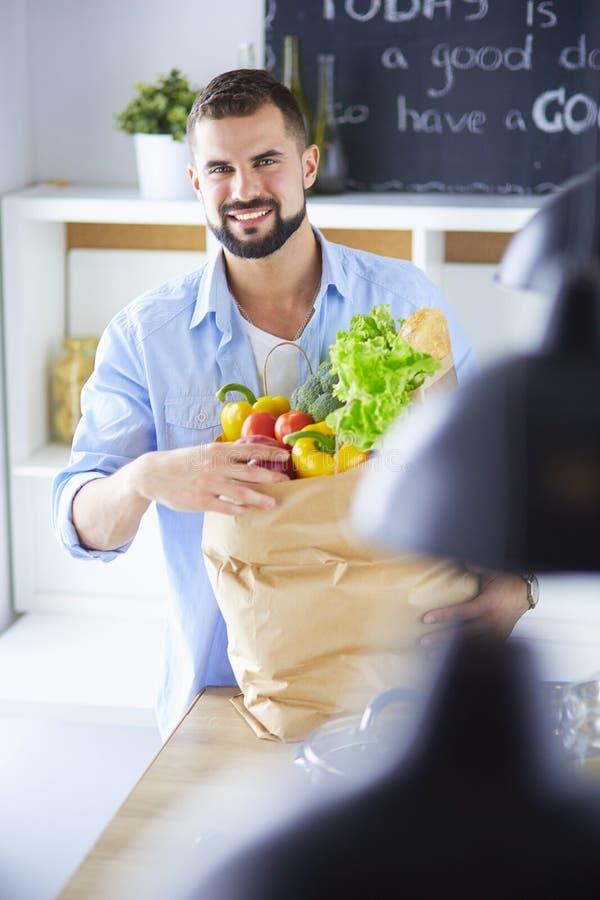 Man den hållande pappers- påsen som är full av livsmedel på kökbakgrunden Shoppa och sunt matbegrepp royaltyfria bilder