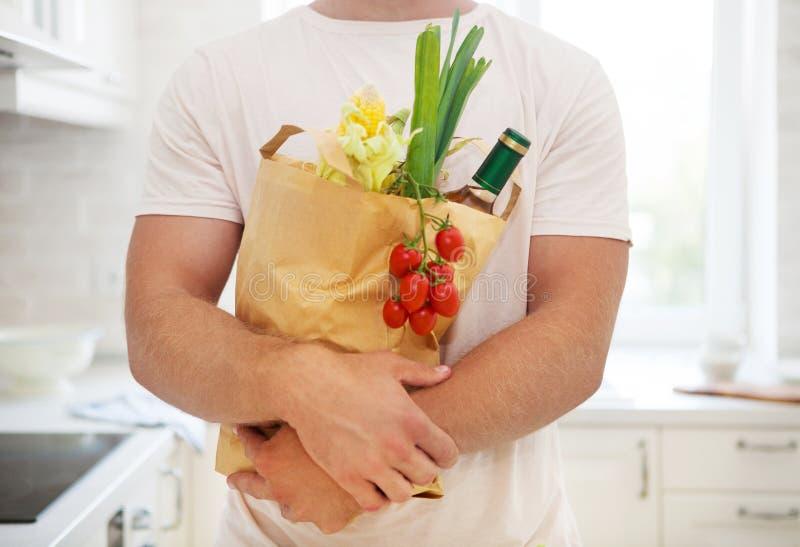 Man den hållande pappers- påsen som är full av livsmedel på köket royaltyfria foton
