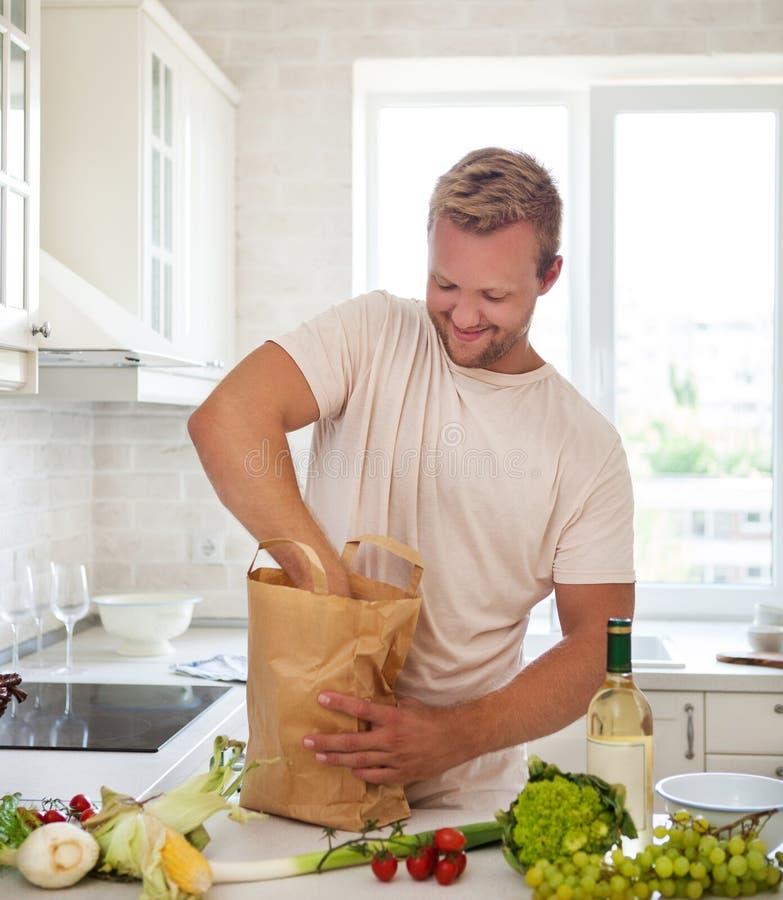 Man den hållande pappers- påsen som är full av livsmedel på köket royaltyfria bilder