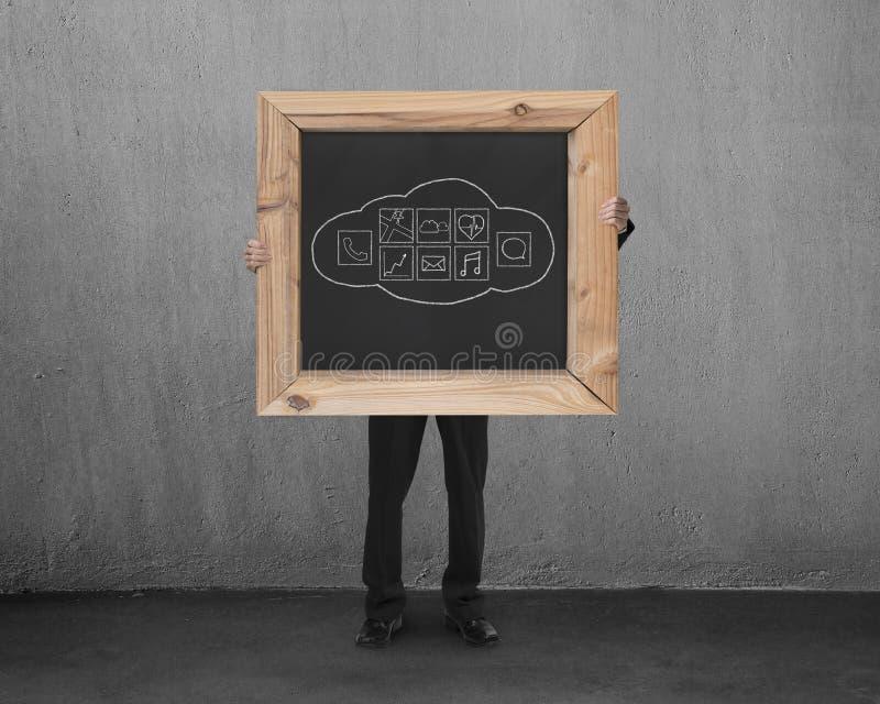 Man den hållande svart tavla med hand-drog app-symboler i konkret roo fotografering för bildbyråer