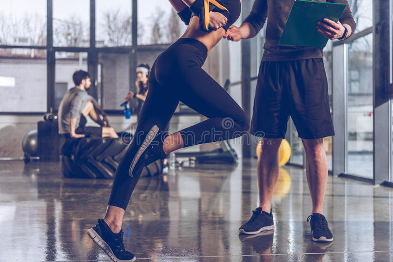 Man den hjälpande sportive kvinnan som övar med trxidrottshallutrustning arkivfoton