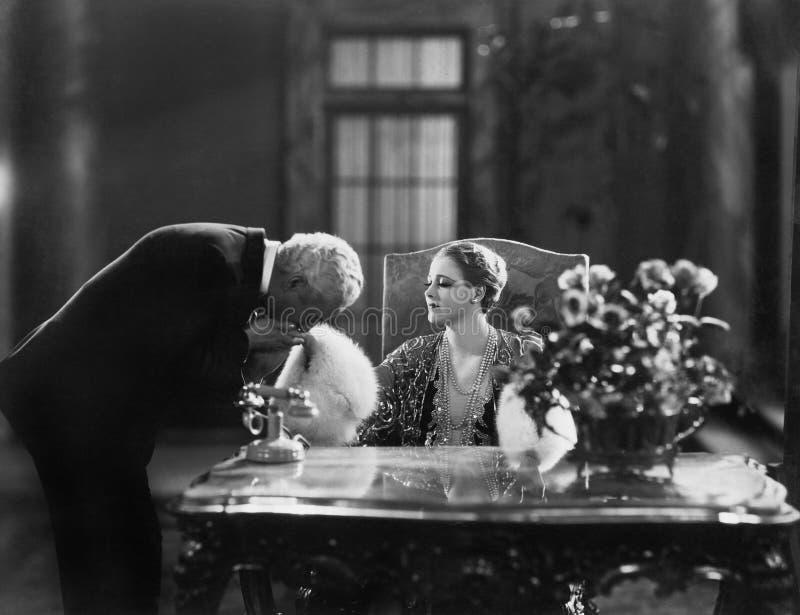Man den kyssande handen av kvinnasammanträde på skrivbordet (alla visade personer inte är längre uppehälle, och inget gods finns  arkivfoton