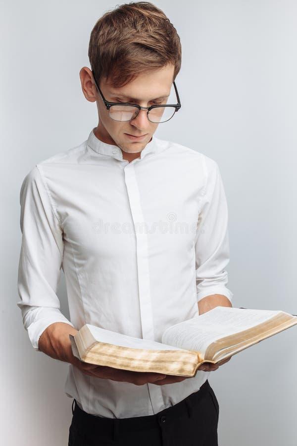 Man den läs- bibeln, vit bakgrund, bok i handnärbild arkivfoton