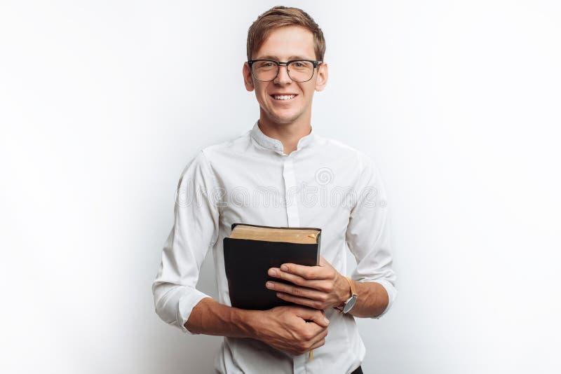 Man den läs- bibeln, vit bakgrund, bok i handnärbild arkivbilder