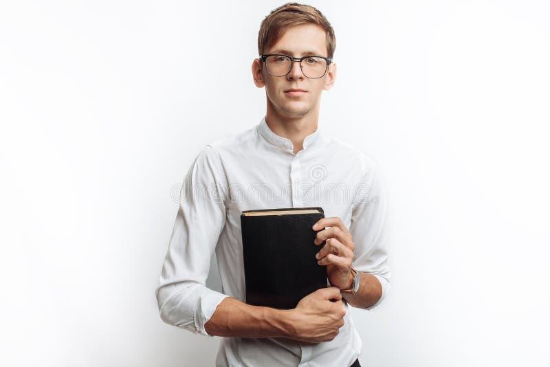 Man den läs- bibeln, vit bakgrund, bok i handnärbild fotografering för bildbyråer