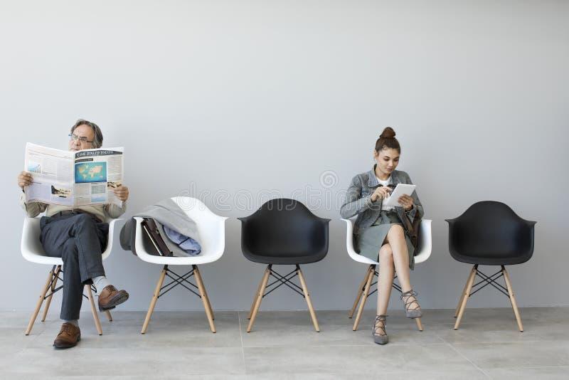 Man den läs- tidningen och kvinnan som använder den digitala minnestavlan arkivfoton