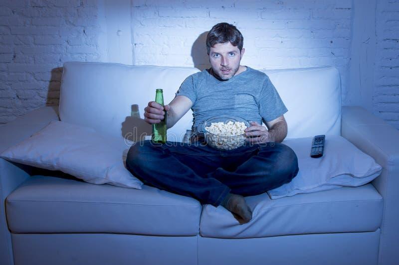 Man den sittande hemmastadda soffan i hållande ögonen på film för vardagsrum eller sporten i tv som äter popcorn och dricker öl royaltyfri bild