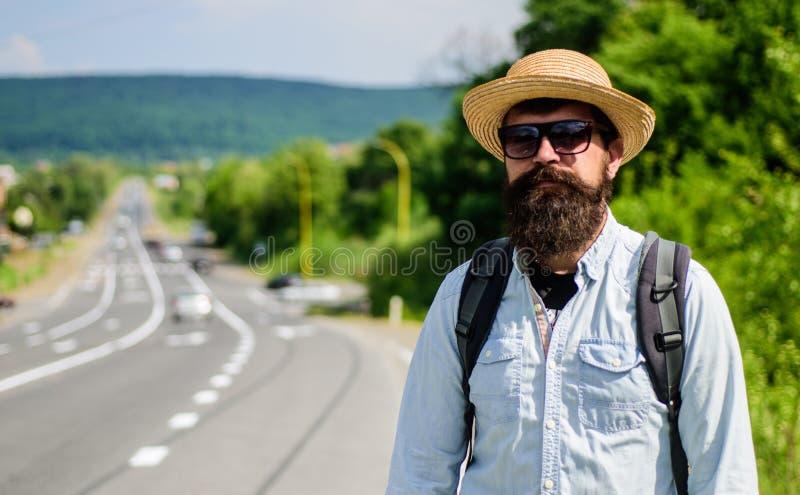 Man den skäggiga hipsterfotvandraren på kanten av huvudvägen jag tar dig Tar den väntande på bilen för handelsresanden honom på n arkivbild