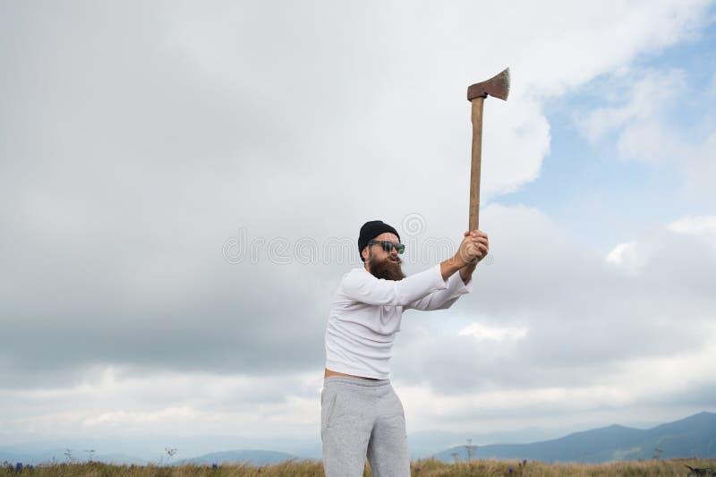 Man den skäggiga skogsarbetaren i solglasögon, hattlönelyftyxa arkivfoto