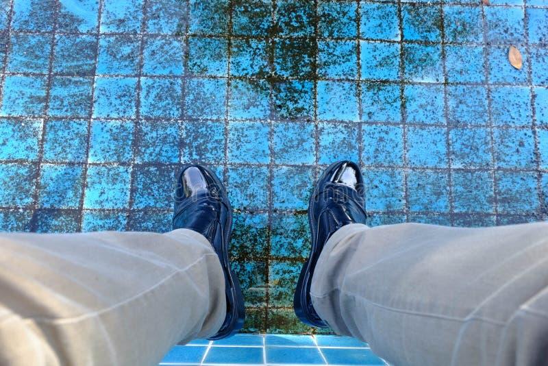 Man den svarta läderskon med lägre ben för brun jeans in i en torr pöl arkivfoto