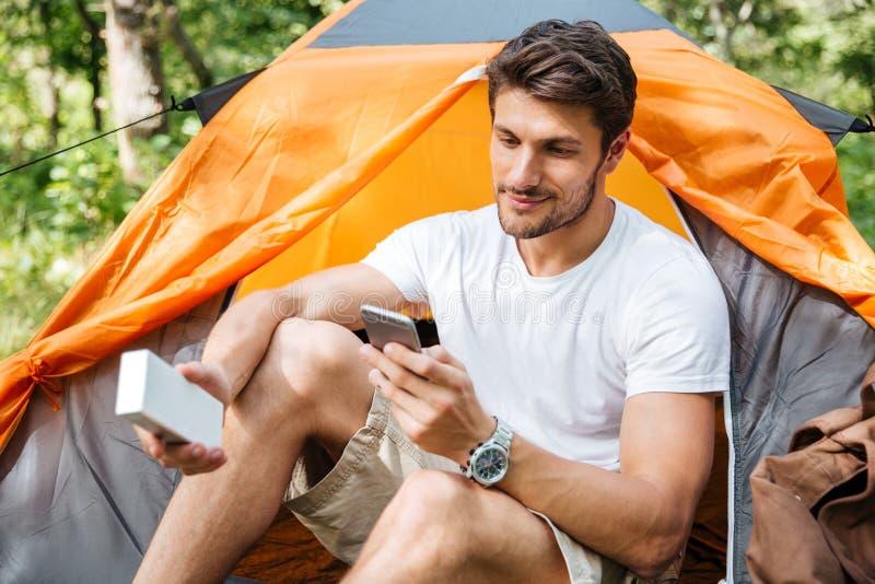 Man den turist- användande mobiltelefonen och den bärbara mini- högtalaren arkivbilder