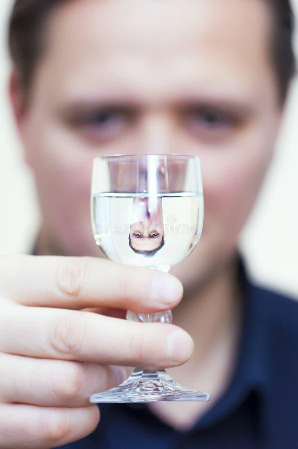 Man den uppochnervända ståendereflexionen för ` s i vodkaexponeringsglasskott royaltyfri bild