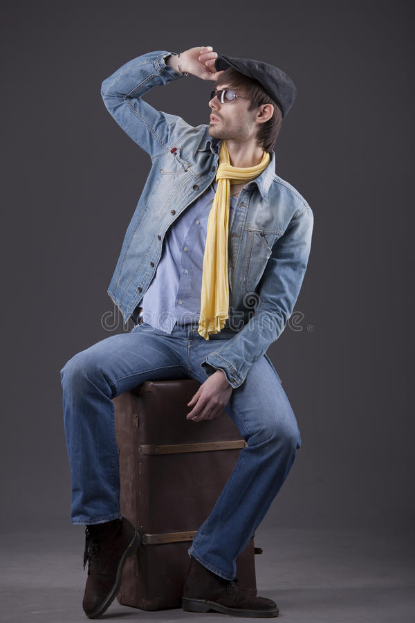Man in denim clothes with suitcase. Fashion man in denim clothes sitting on old suitcase royalty free stock image