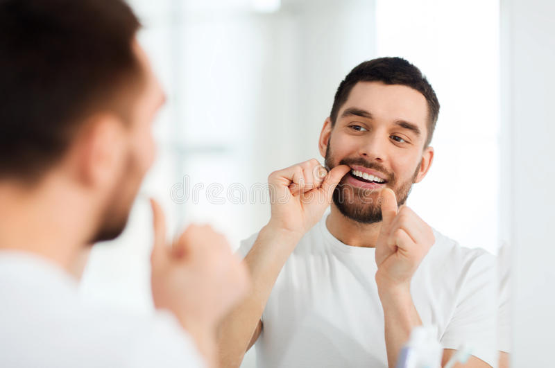 Man with dental floss cleaning teeth at bathroom. Health care, dental hygiene, people and beauty concept - smiling young man with floss cleaning teeth and royalty free stock image