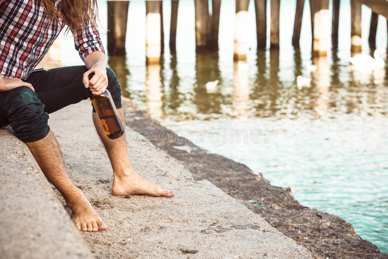 Man depressed with wine bottle sitting on beach outdoor. Man depressed with wine bottle sitting on sea shore outdoor. People abuse and alcoholism problems stock images