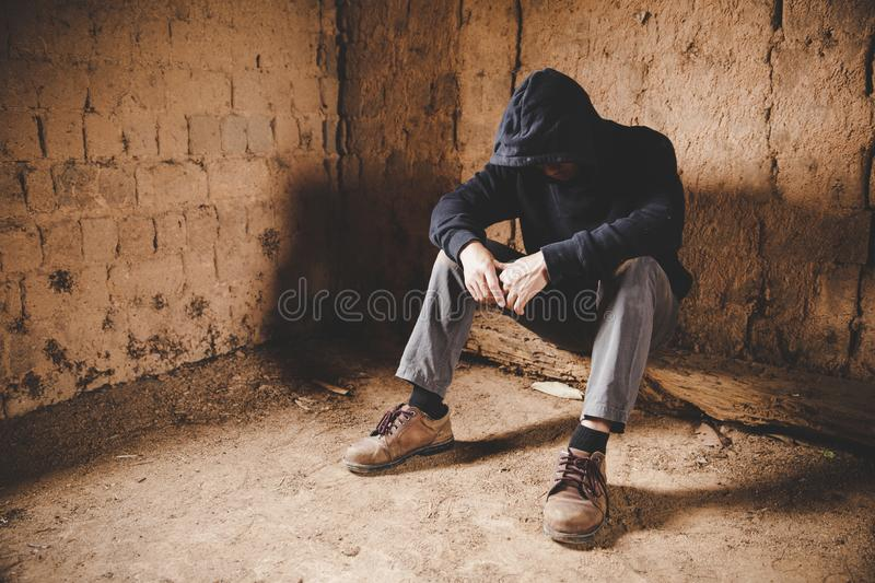 A man in a depression on the streets. The concept of drug abuse and traffic stock image