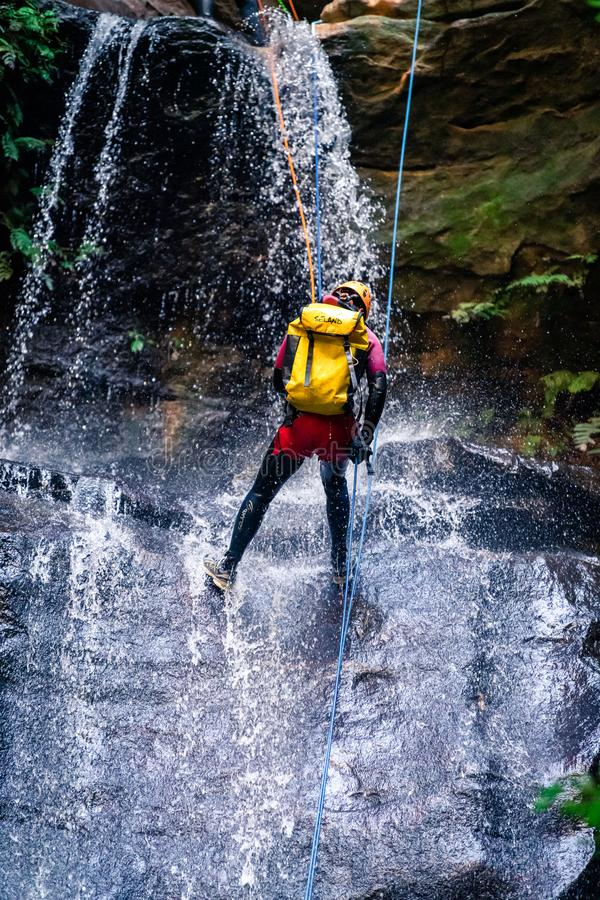 Man descending down long drop cascading waterfall over slippery rocks, wearing backpack, with rope, wetsuit, helmet and climbing stock photo