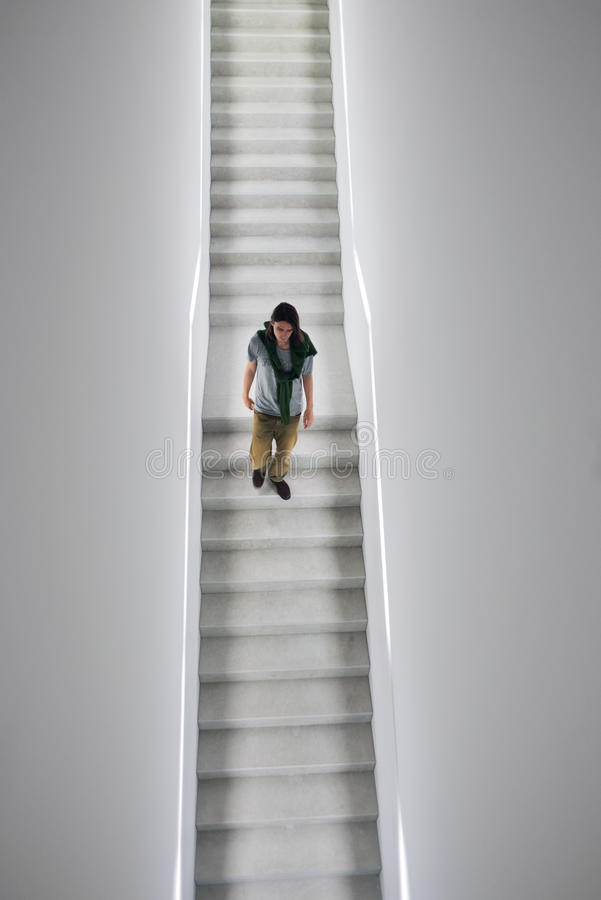 Man descending staircase in white cube gallery. Man descending white stairs in white cube gallery royalty free stock image